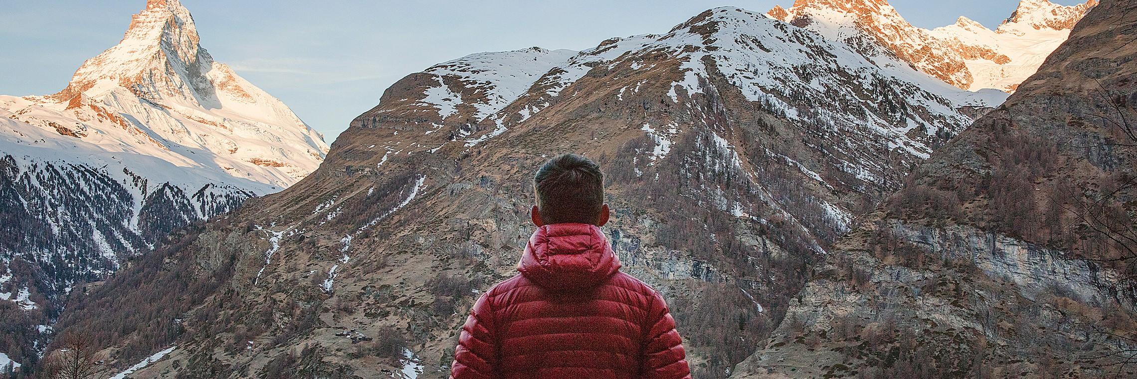 Man In Red Jacket Looking At The Alps In Zermatt Switzerland